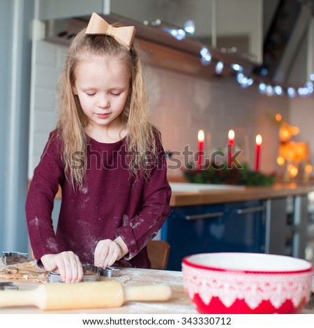 Little adorable girl baking Christmas cookies at home
