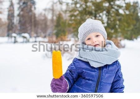 Little adorable girl eating tasty corn in winter day - stock photo