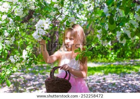 Little adorable girl in blossoming apple tree garden - stock photo