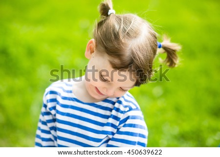 Little adorable girl in striped T-shirts outdoors on warm and sunny summer day - stock photo