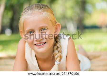 Little adorable girl lying in summer park - stock photo