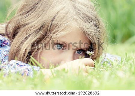 Little adorable girl lying on grass looking at daisy - stock photo