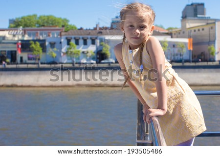 Little adorable girl on the deck of a ship sailing in big city - stock photo
