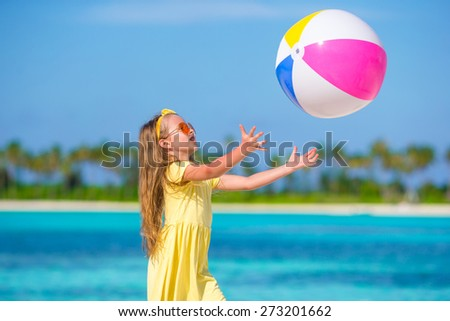 Little adorable girl playing on beach with ball - stock photo