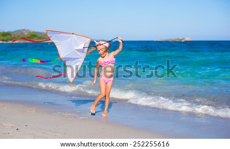 Little adorable girl playing with flying kite during tropical beach vacation - stock photo