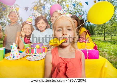 Little adorable girl playing with party blower