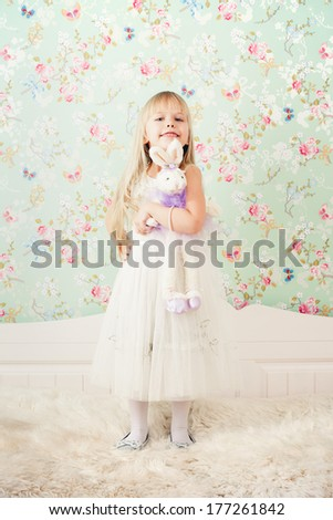 Little adorable girl playing with rabbit toy - stock photo