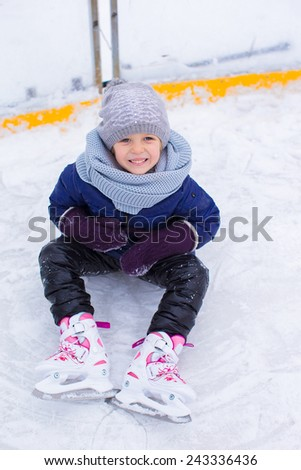 Little adorable girl sitting on ice with skates after fall - stock photo