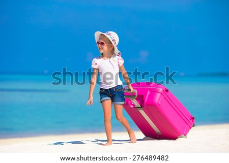 Little adorable girl with big bag on white beach  - stock photo