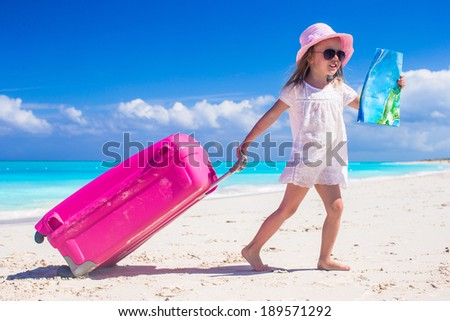 Little adorable girl with big colorful suitcase and a map in hands on tropical beach - stock photo