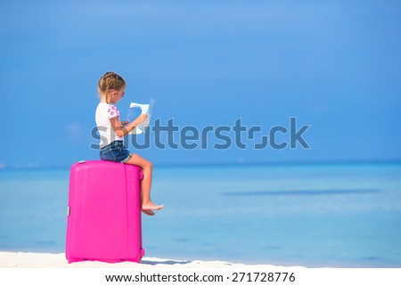 Little adorable girl with big luggage and map of island on white beach - stock photo