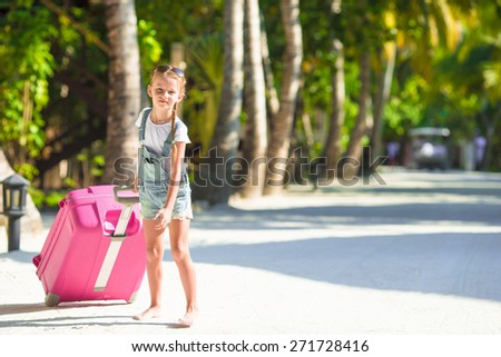 Little adorable girl with big luggage during summer vacation - stock photo