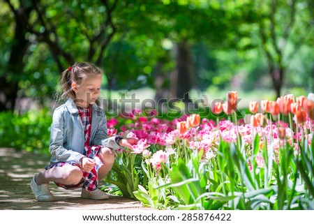 Little adorable girl with flowers in tulips garden  - stock photo