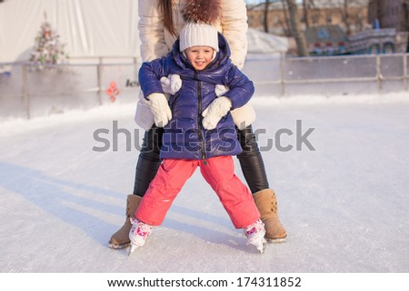 Little adorable girl with her mom learning to skate - stock photo