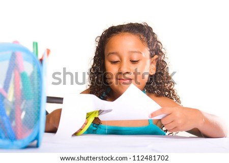 Little adorable girl working with scissors at her desk - stock photo