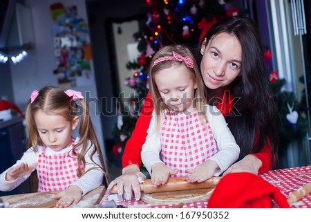 Little adorable girls and young mother baking Christmas gingerbread cookies