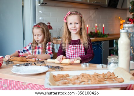 Little adorable girls baking gingerbread house on Christmas eve
