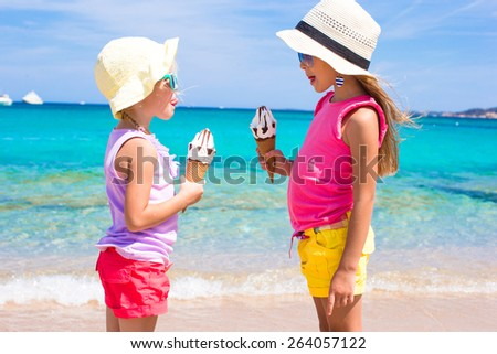 Little adorable girls eating ice cream on tropical beach - stock photo
