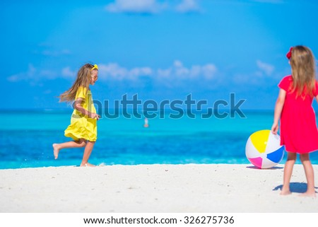 Little adorable girls playing on beach with air ball - stock photo