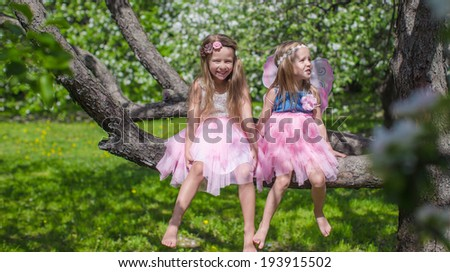 Little adorable girls with butterfly wings on blossoming apple tree - stock photo