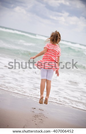 Little adorable kid girl in striped dress jumping on the sandy beach and having fun at the ocean. Sea vacations. Child dreaming. Outdoors. Back view. - stock photo