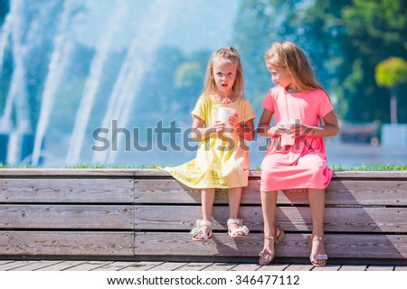 Little adorable kids eating ice cream on summer hot day - stock photo