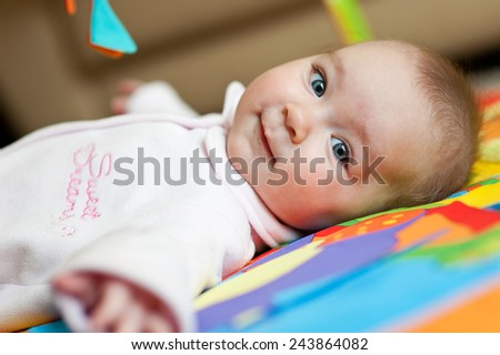 Little adorable newborn infant baby girl lying on back on colorful carpet and looking in camera indoors - stock photo
