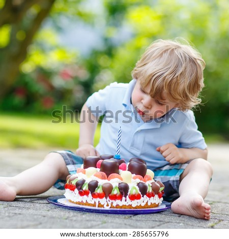 Little adorable toddler child celebrating his 3 birthday in home's garden with big cake. Happy kid boy laughing about gifts and tasting cake. Outdoors on sunny day. - stock photo