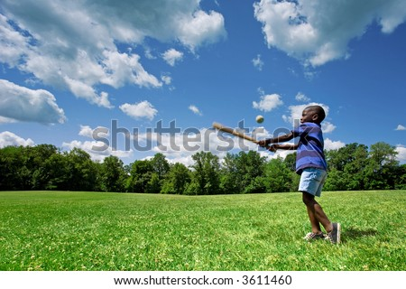 Little African American boy playing baseball in a sunny field on a beautiful summer day.