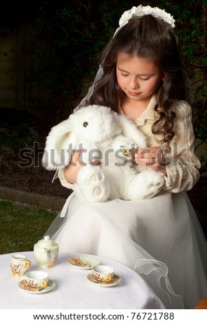 Little Alice in Wonderland girl drinking tea with a white rabbit - stock photo