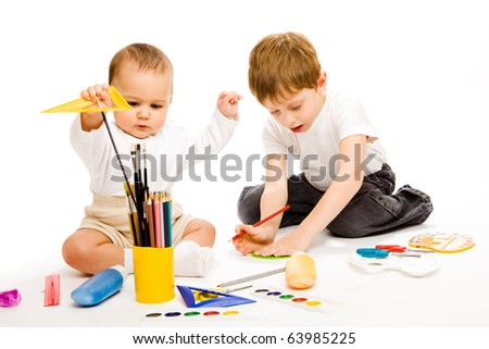 Little and preschool brothers drawing, isolated - stock photo