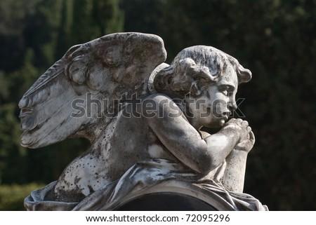 little angel lying outdoors - stock photo