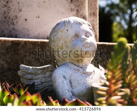 Little angel statue in front of a grave among the flowers - stock photo