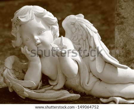 little angel with butterfly, statue in sepia - stock photo