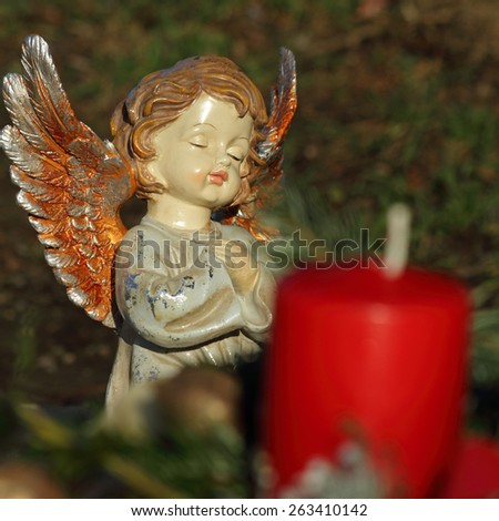 little angelic ceramic  figurine and candle on catholic cemetery, Vienna - stock photo