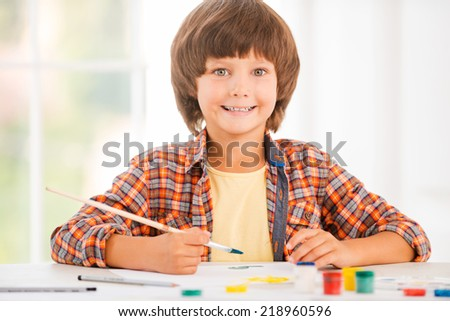 Little artist. Happy little boy relaxing while painting with watercolors sitting at the table - stock photo