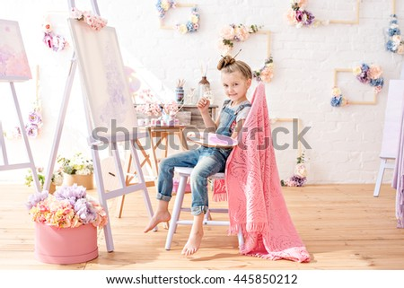 Little artist in denim overalls painting brushes on the easel in her studio - stock photo