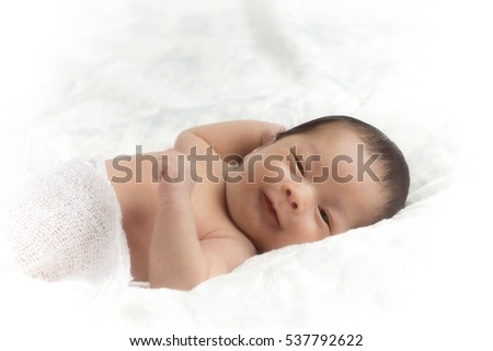 Little asia newborn baby boy 15 days lying on a bed with soft focus