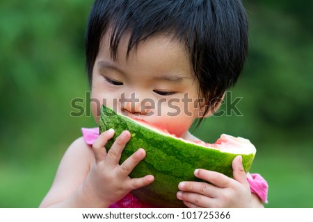 Little Asian baby eating watermelon in park - stock photo