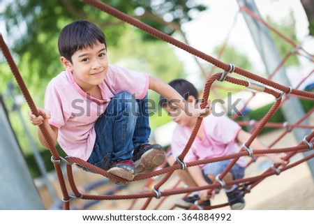 Little asian boy climbing rope obstacle activity on the playground - stock photo