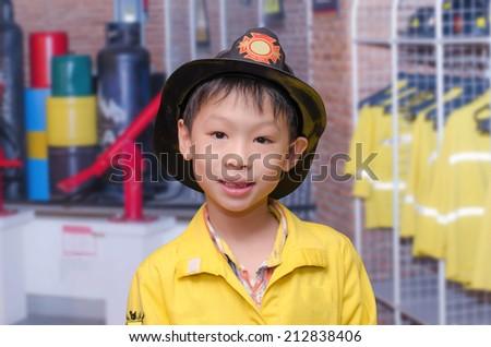 little Asian boy in firefighter uniform  - stock photo