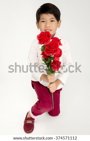 Little Asian boy in vintage suit with red rose and giving red flowers. Over gray background with smile face