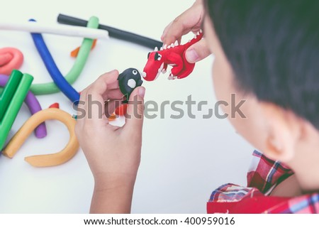Little asian boy playing and creating toys from play dough. Child molding model clay. Strengthen the imagination of child. Vintage style. Cross process. - stock photo
