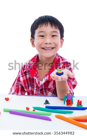 Little asian boy playing and creating toys from play dough. Child smiling and show his works from clay on hand, on white background. Strengthen the imagination of child - stock photo