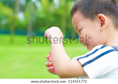 Little Asian boy playing bubbles wand at outdoor - stock photo
