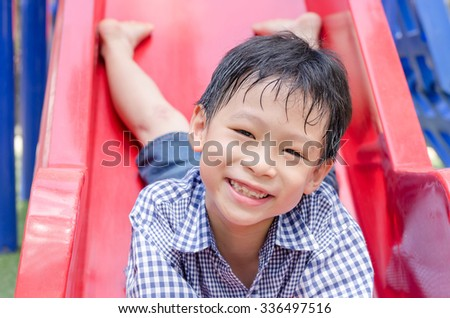 Little Asian boy playing slider at playground