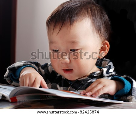 little asian boy reading book - stock photo