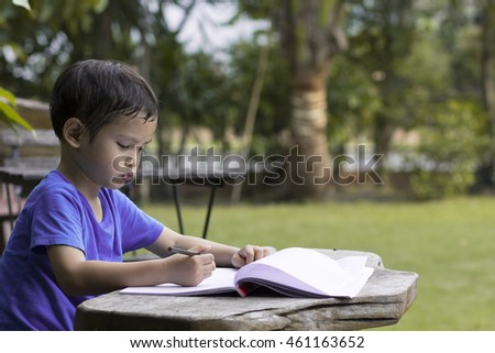 Little asian boy use pencil writing on notebook for writing book  on wooden table in the park