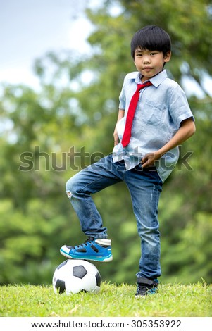 Little asian boy with football at the park,Bangkok Thailand