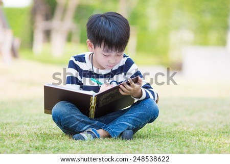 little asian boy writes homework in the garden - stock photo